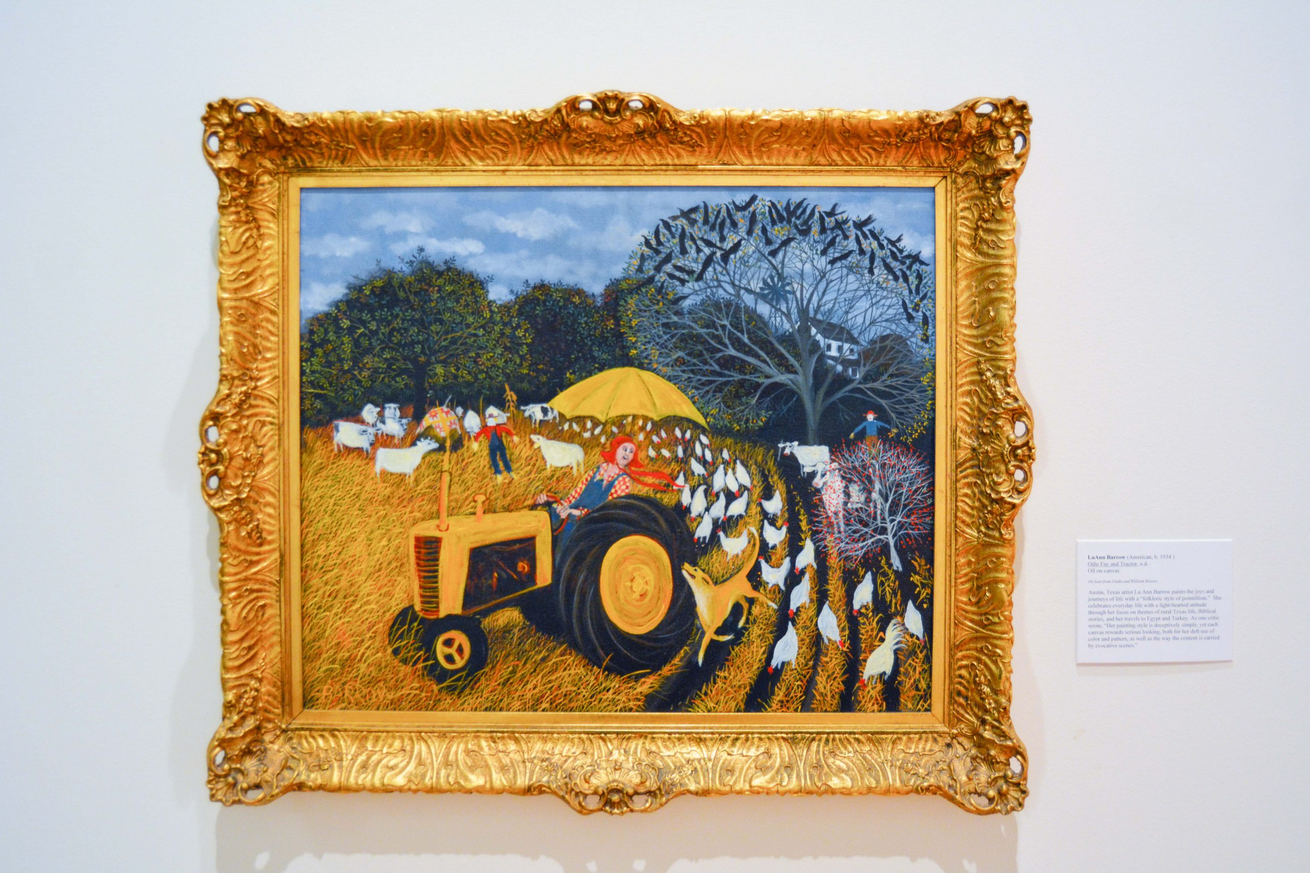 Woman in overall and red hat on tractor with dog running beside her and chickens eating