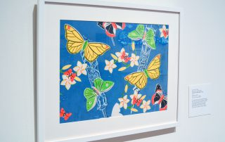 Framed print of butterflies in yellow, green, and red/black on a blue background