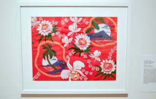 Framed print of blue volcanoes, white flowers, and green palm trees on a red background