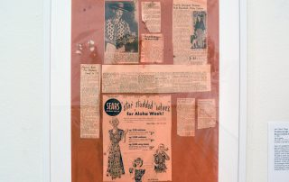 Framed newspaper clippings of John Meigs and an old advertisement for Sears featuring illustrations of women and girls in Aloha themed dresses and tops