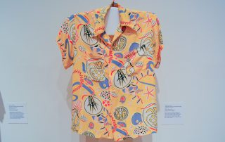 An Aloha shirt with white and blue abstract images on a yellow background