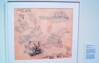 """Original drawings on tracing paper showing a woman and a boat anchor, barrels of goods, a man in a straw hat, a hut with a sign that says """"Trader Joe's"""", and a ship"""